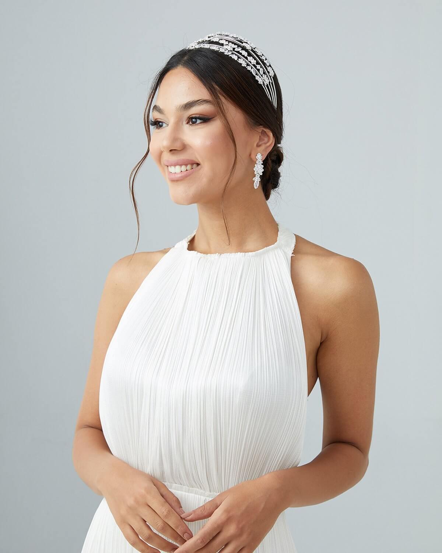 Si buscas lucir un estilo minimalista para tu tocado, el modelo Marisha es genial, con acabados en pedrería de zircones, este cintillo de novia de hará lucir impecable