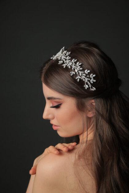Tocado de novia hecho de sobrio hilo plateado con pequeños adornos brillantes, que enmarca el peinado recogido, con delicadas formas geométricas combinadas con motivos florales que te harán relucir en tu boda en Venezuela