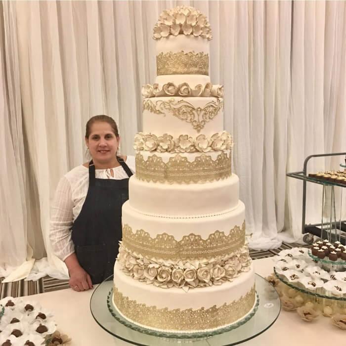 Andreina Martin posando junto con una de sus majestuosas creaciones: un espectacular pastel de bodas en Margarita, Venezuela