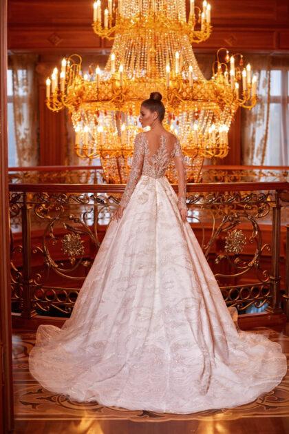 El vestido combina armoniosamente dos tipos de encaje: uno muy fino, incluso delicado, y otro ricamente bordado con aplicaciones voluminosas